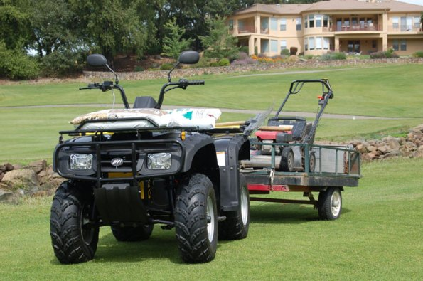 ZAP DUDE electric ATV used for golf course maintenance towing a lawnmower.
